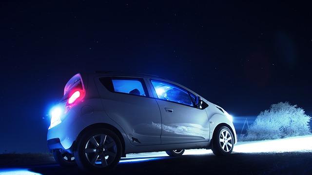 Biele auto v tme s hliníkovými diskami svieti prednými svetlami do diaľky