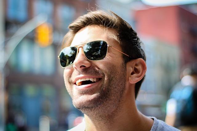 Muž v slnečných okuliaroch sa usmieva