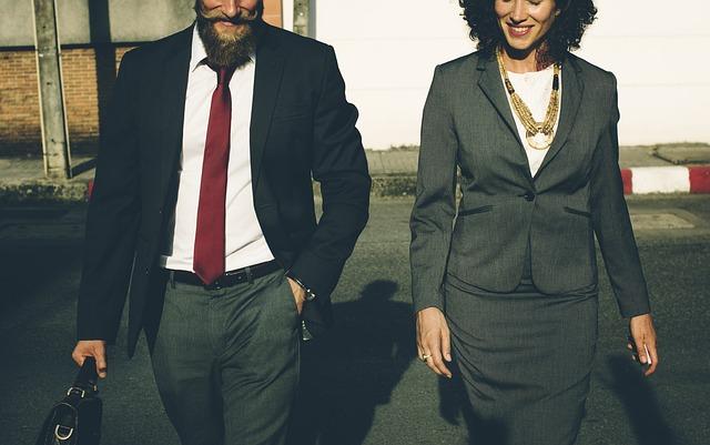 Usmiaty muž a žena v elegantnom oblečení kráčajú spolu po ceste
