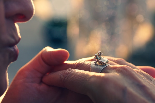 Muž bozkáva žene ruku, na ktorej má strieborný prsteň so žabou