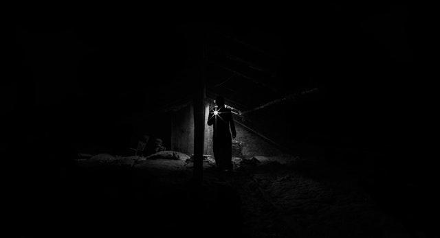 Človek v tme svieti baterkou.jpg