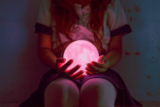 Žena v sukni drží na kolenách guľatú lampu.jpg