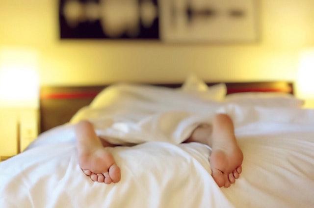 Človek leží na posteli a z pod plachty mu trčia holé chodidlá