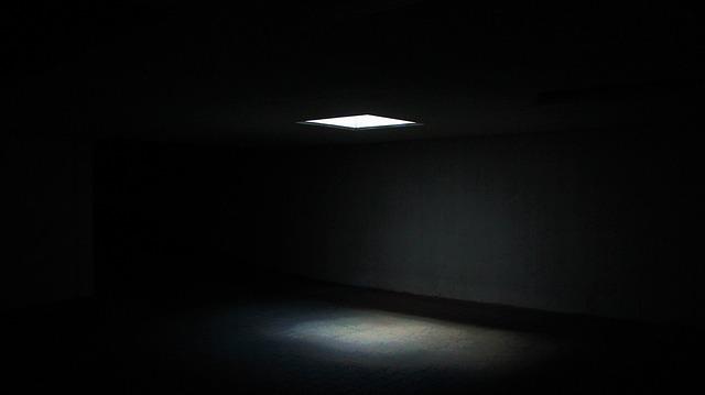 Tmavá miestnosť so zapáleným svetlom na strope